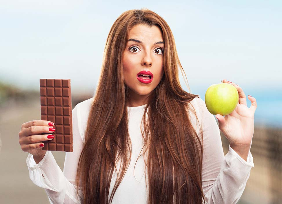 portrait of a pretty girl choosing between chocolate or an apple