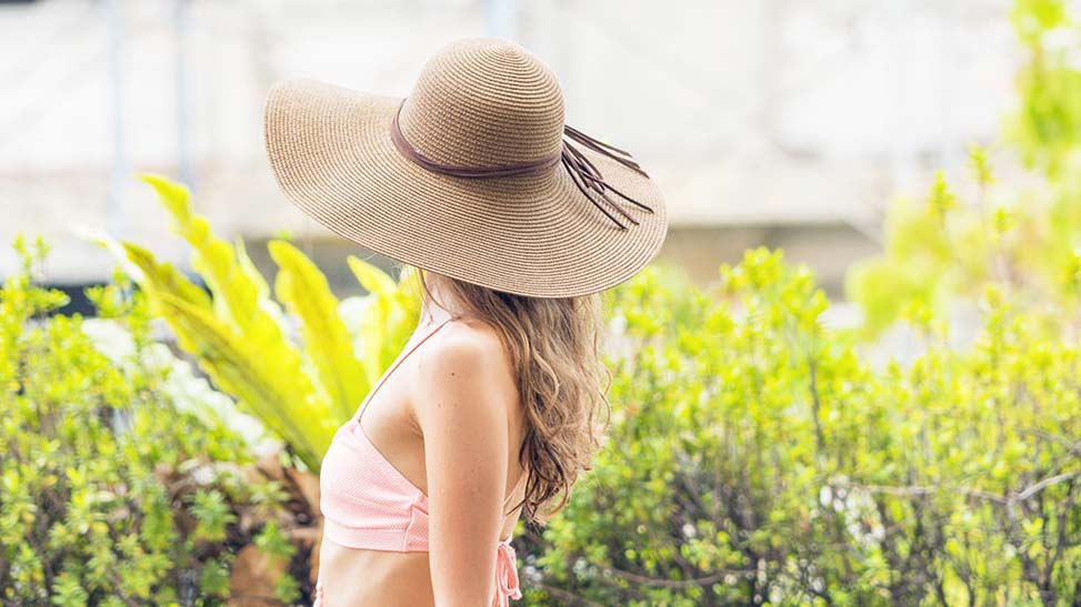 Smiling woman at swimming pool, wearing straw hat and swim wear.